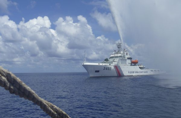 Chinese Coast Guard members approach Filipino fishermen as they confront each other off Scarborough Shoal in the South China Sea, also called the West Philippine Sea, on Sept. 23, 2015. (AP Photo/Renato Etac)